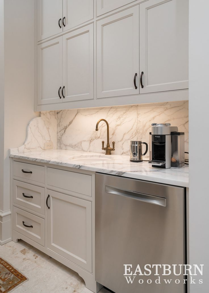 Home coffee bar with white painted cabinets and stainless steel