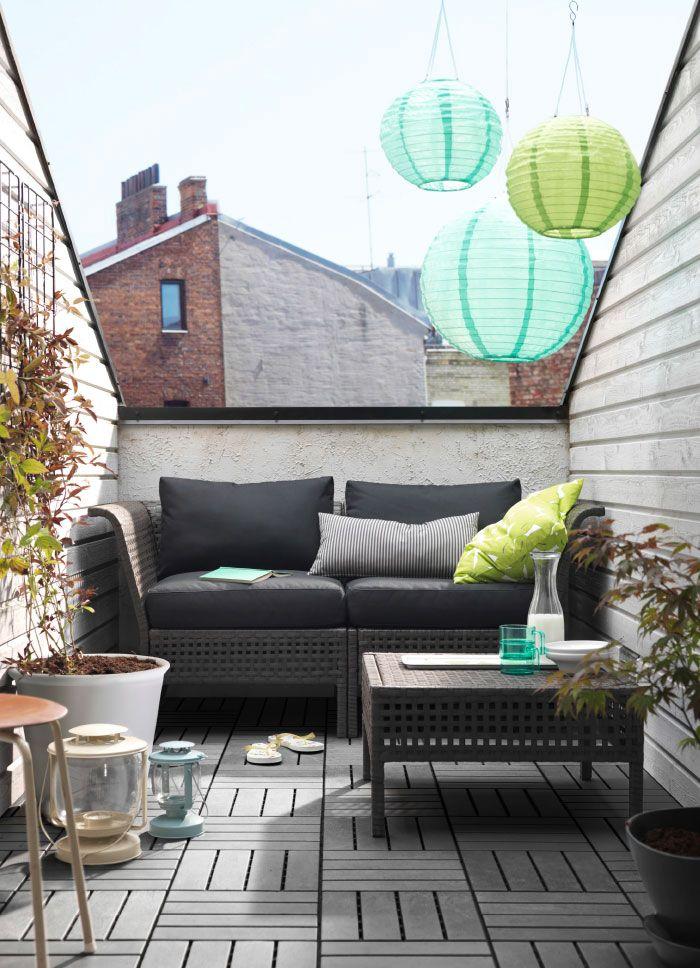 Tiny, small balcony. Balcón pequeño con un sofá de dos plazas negro con cojines y una mesa de centro.