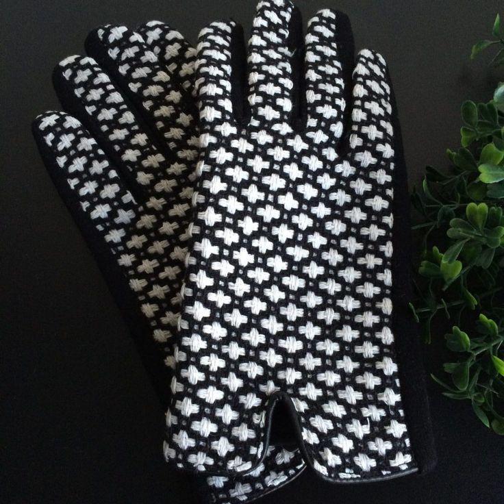 Deze zwart met witte handschoenen van stof hebben aan de bovenzijde een geweven motief. Witte kruisjes. Onderzijde is zwart. Bij de pols is een inkeping.
