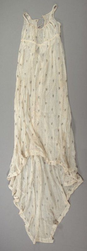 Dress ca. 1795–1810 Sheer Cotton; Wrapped Silver Gilt Thread Embroidery. England. Dress of sheer cotton embroidered with silver thread in alternating vertical bands of meandering lines and floral sprigs: narrow empire waisted bodice; narrow band of self fabric at waist; drawstring neckline ties at center back neck; sleeveless; narrow shoulder straps; trained skirt. Fine arts museums of San Francisco