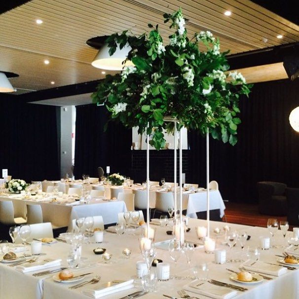 White stand with a foliage based arrangement and pops of white floral | Bouquet Melbourne | (venue: Encore St Kilda)