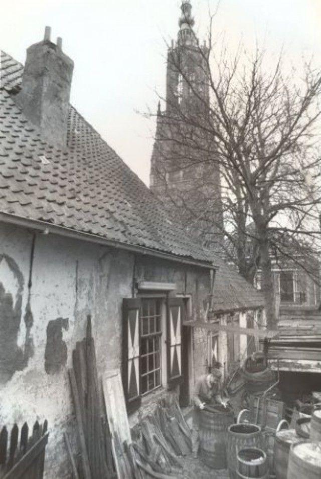 De zijgevel van Hellestraat 7, waar kuiperij Meester gevestigd is. Tussen de tonnen en kuipen staat Marinus Meester.
