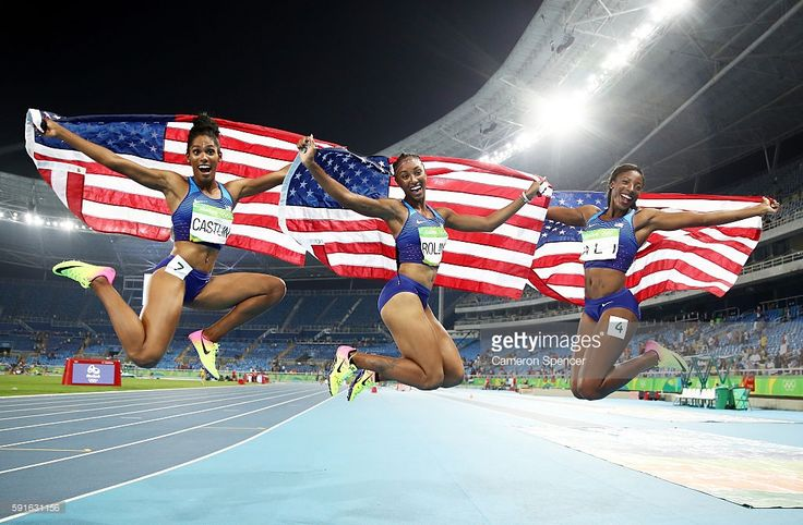 Bronze medalist Kristi Castlin, gold medalist Brianna Rollins and silver medalist Nia Ali of the United States celebrate with American flags after the Women's 100m Hurdles Final on Day 12 of the Rio 2016 Olympic Games at the Olympic Stadium on August 17, 2016 in Rio de Janeiro, Brazil.