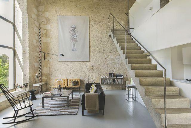 Baignée de soleil, la pièce à vivre associe des murs de pierre à un majestueux escalier en béton