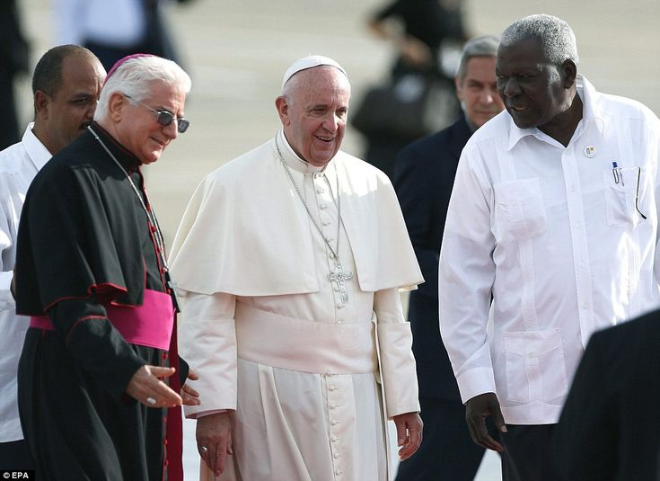 Pope Francis (C) speaks with Archbishop Dionisio Guillermo Garcia (L) and President of Cuban Parliament, Esteban Lazo (R), upon his arrival at the airport