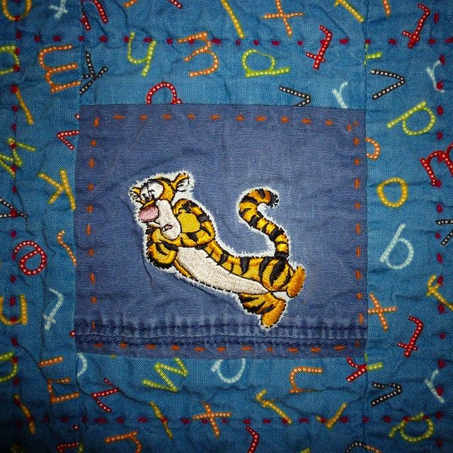 Detail of quilt by Nadine Flagel. Fabric can work so much harder than we give it credit for. This Tigger from my son's t-shirt quilt was originally on an infant t-shirt he wore a few times before outgrowing it. I saved it and used it to patch the ripped knee of a pair of his blue pants. Then I turned the pants into shorts and saved this bit for the quilt.