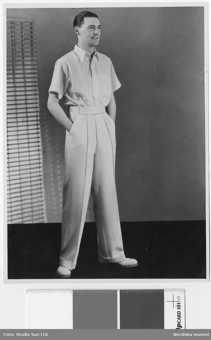 Man i vit, kortärmad krage och vita byxor med bred linning och markerade pressveck. Vita skor. Nordiska Kompaniet. Fotograf: Studio Sun Ltd