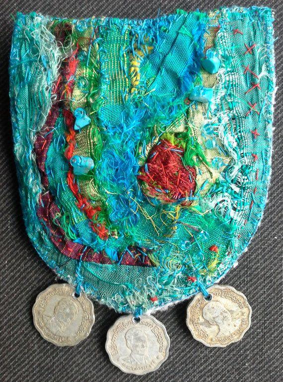 Oprichting van textiel juweel Bobo, Ethno, Chic. Textiel pin zet op een kledingstuk bijvoorbeeld een jas of een jas. Realisatie van wild silks fragmenten uit Indiase saris hand genaaid. Deze trinket is versierd met kleine stenen turkoois en versierd met 3 delen zilver afkomstig uit Thailand. Het creëren van unieke en originele 7x10cm. PIN in tinten van groen, turkoois en rood.  Oprichting van textiel juweel Bobo, Ethno, Chic. Textiel pin zet op een kledingstuk bijvoorbeeld een jas of een…