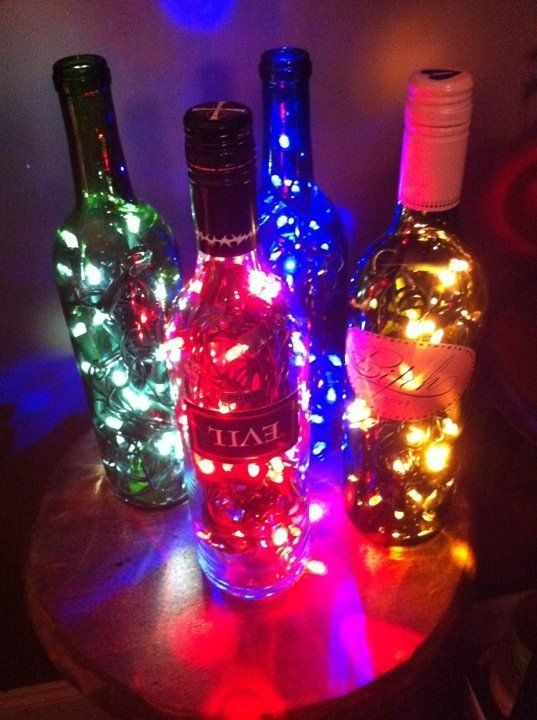 Wine bottle lamp made with Christmas lights. Drill a hole in the bottom/back for the cord.  Using colored glass has a nice effect.