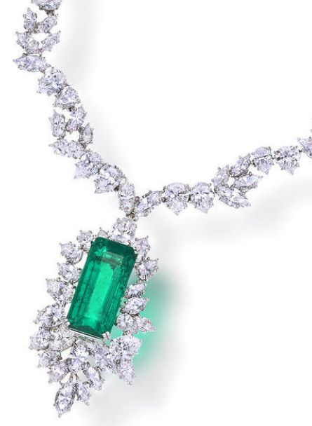 An emerald and diamond necklace, Harry Winston. Designed as cut-cornered rectangular-cut emerald, weighing 13.45 carats, within a pear and marquise-cut diamond cluster surround, completed by a similarly designed necklace; necklace signed Winston, pendant signed HW for Harry Winston; with signed box; estimated total diamond weight: 32.00 carats; mounted in platinum and eighteen karat white gold; length: 16in. Via Bonhams.