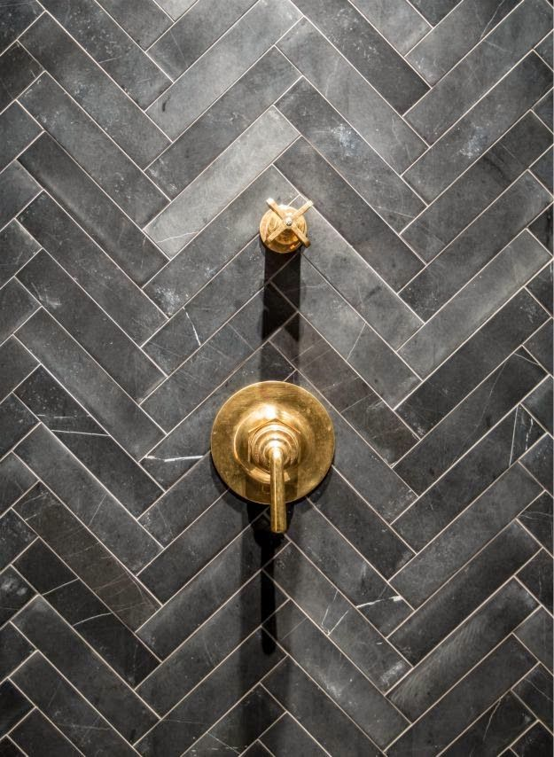 honed grey stone rectangular tile laid in a chevron pattern with aged brass plumbing fixtures