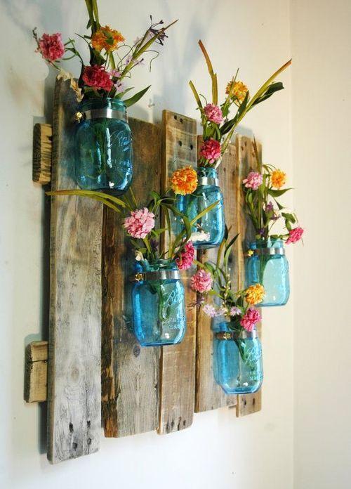 Panneau mural en planches de récupération sur lequel sont fixés des pots en verres bleus servant de vases
