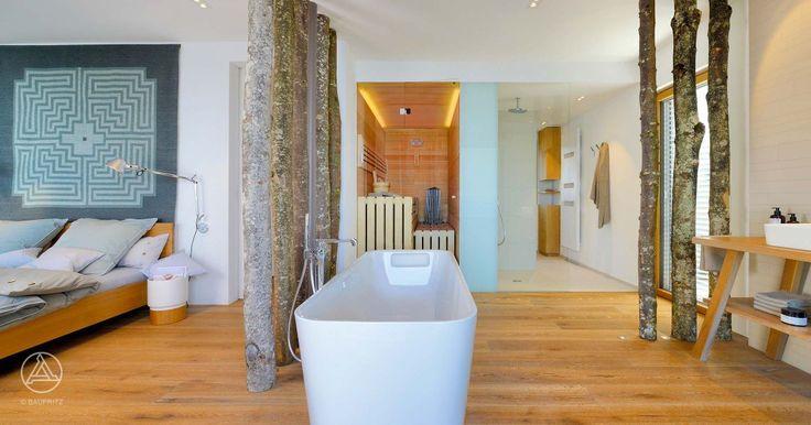 Baufritz Musterhaus Haus am See – Offenes Badezimmer mit direkter Angrenzung an das Schlafzimmer, freistehende Badewanne und tropenholzfreie Bio-Sauna