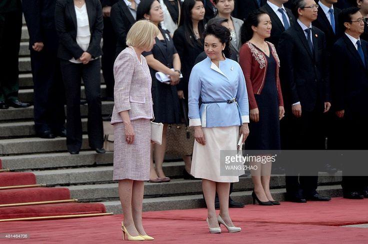 Peng Liyuan (R), wife of Chinese President Xi Jinping, looks at ...