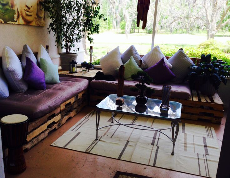 Wood pallets and twin mattress sectional couch bed screened porch bohemian room.
