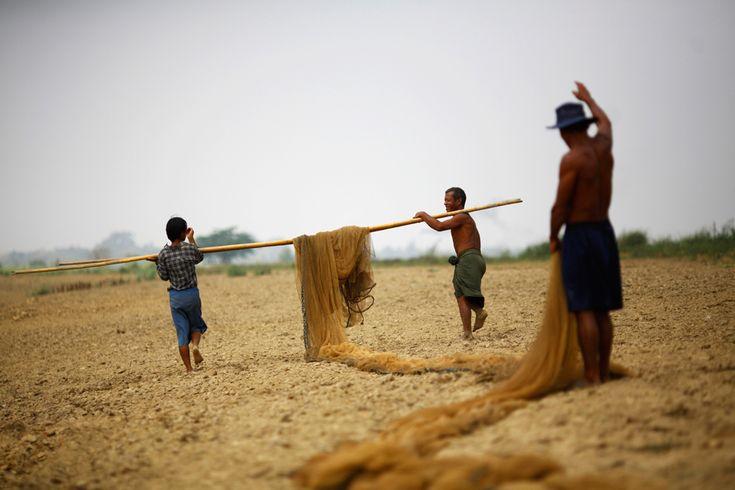 Fishermen carry their nets on a bamboo pole to dry them out in the sun after fishing at the Bago River on March 20, 2012. (Staff/Reuters) #
