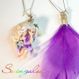 Pendant earrings, the pair consists in a Swingaloo fairy on a moon that glows in the dark and a purple synthetic feather. 100% Made in Italy! These jewels are completely handmade by an italian artist, the earwires are made of silver plated alloy with a secure and durable closure. Find it on www.Delicute.com