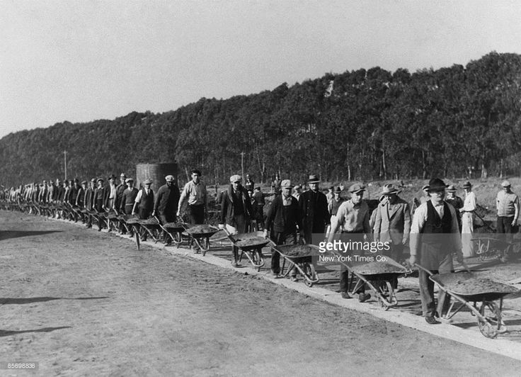 Civil Works Administration workers on their way to fill a gully with wheelbarrows of earth during the construction of the Lake Merced Parkway Boulevard, under President Franklin D. Roosevelt's New Deal, San Francisco, California, 1934.