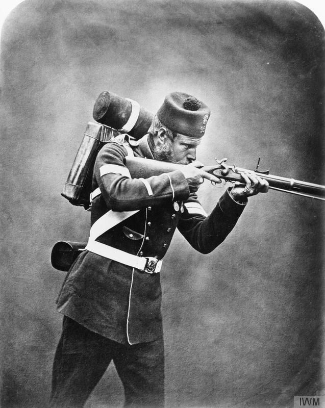 Crimean War veteran portrait of Corporal James Tinn, 95th Regiment, wearing pack and aiming his rifle. © IWM (Q 71639)