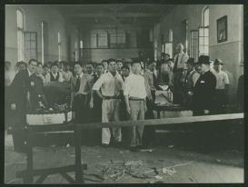 Imigrantes japoneses no interior do armazém de bagagens ou setor de bagagens, como foi denominado posteriormente, ajudando os funcionários da Hospedaria do Brás na conferência dos itens trazidos na viagem.