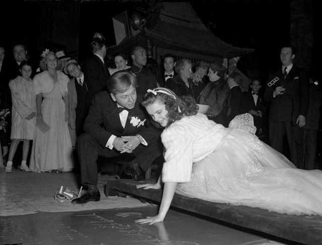 Mickey Rooney watching Judy Garland put her handprints in cement at Grauman's Chinese Theatre, 1939