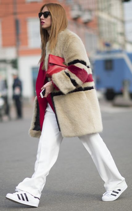 A striped fur coat paired with athletic sneakers.
