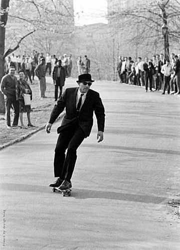 skateboarding down the hill. clay wheel danger. cool suit and dress shoes.