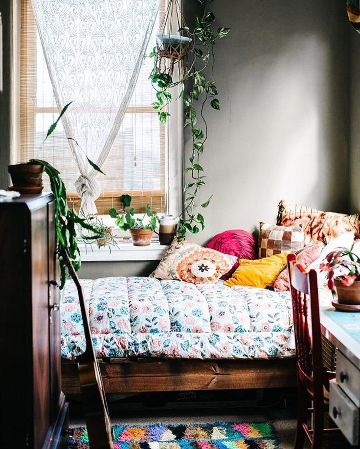 Bohemian sunroom/guestroom with patterns and plants.
