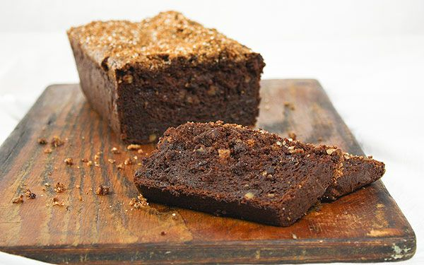A photo of Chocolate-Banana Walnut Bread displayed on a dark wooden board with two cut slices.