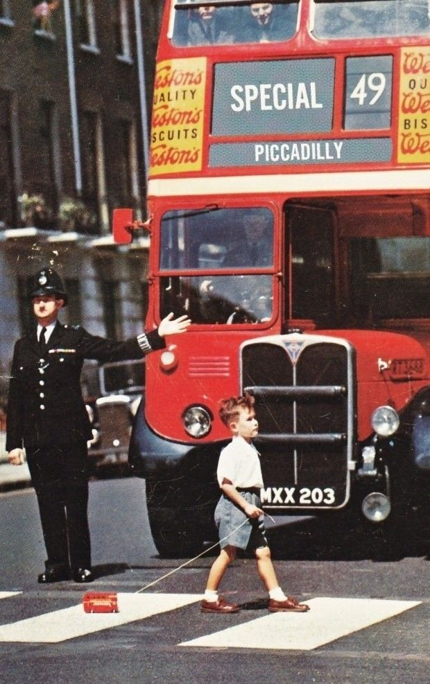 A boy crosses a London street in the 1960s with a toy double decker