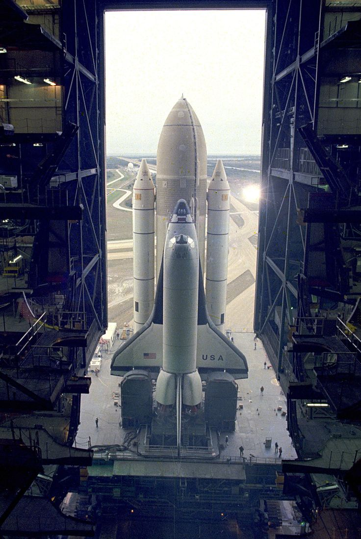 Shuttle Columbia: The first Space Shuttle vehicle destined to fly in space inches out of the Vehicle Asembly Building on its way to Pad A at Complex 39, where it will be launched. The STS-1 vehicle - consisting of America's first reusable spaceship, Columbia, the external propellant tank and twin solid rocket boosters - was assembled on a Mobile Launcher Platform in the Vehicle Assembly Building. A six-million-pound tractor, called the Crawler-Transporter, is used to carry the Space Shuttle…