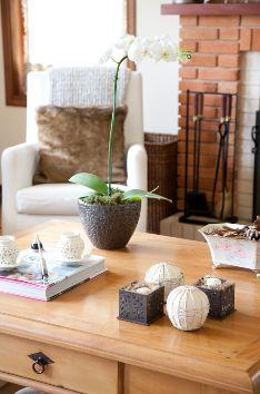 Decoração para mesa de centro em casa estilo rústico chic. Mesa de centro em madeira de demolição, lareira  em tijolo , almofadas em pele e manta de lã. Projeto de decoração e design de interiores em Campos do Jordão, São Paulo.