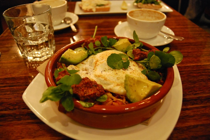 vancouver brunch: medina:   baked egg over curried orzo with hungarian chorizo, red pepper, roasted corn, zucchini, grano padano topped with watercress, avocado and tomato salad