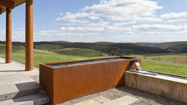 The rural modern house features a courtyard framed by a corten and concrete fountain. An ipe bridge spans a reflecting pool connecting to crushed stone.