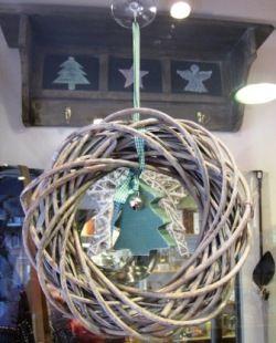 Corona navideña. Al fondo, perchero de madera con estante superior.