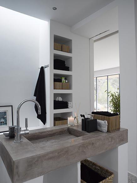 De inhammen in de muur die als open kast functioneert en de strakke betonnen wasbak zijn de neusjes van de zalm in deze badkamer.