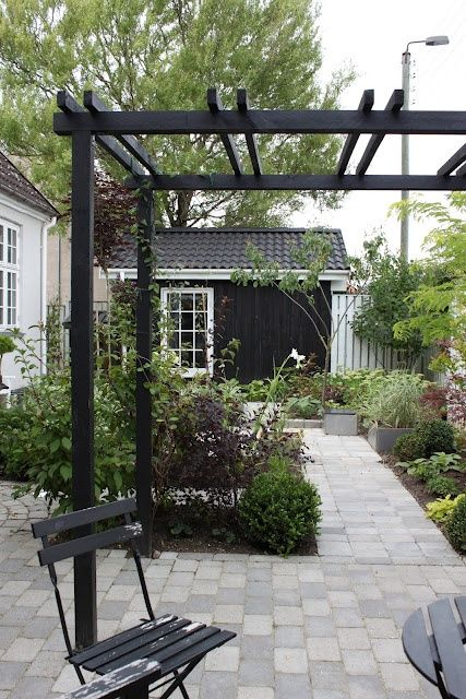 loves me a black shed and paver patio surrounded by gardens and potted plants, vs grass ...
