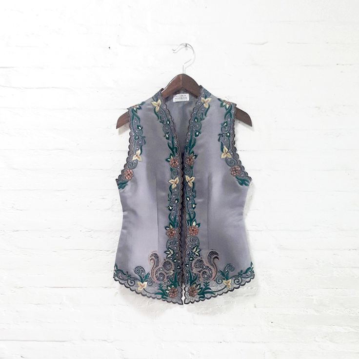 Candy Squirrel 001  IDR 795.000  Open for Pre-Order  Estimated Work Days : 7 – 10 working days  Candy Squirrel Hand Embroidery Contemporary Kebaya Vest  Length of Kebaya : (Front) approx. 70 cm / (Side) approx. 56 cm  Material used : Thick Dove Satin / Hand Embroidery  Free Size (Bust fit to 82 – 94 cm)  *Note: No button added on vest at the front