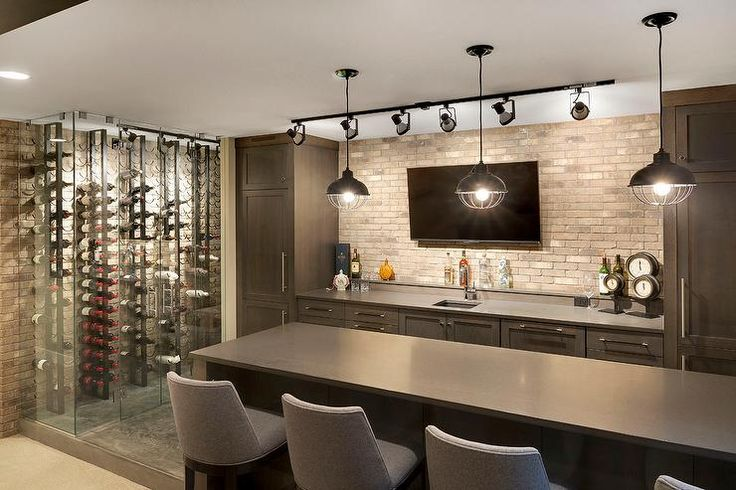 Contemporary basement bar features dark brown cabinets paired with gray quartz countertops and a brick backsplash lined with a flat panel tv illuminated by track lighting.