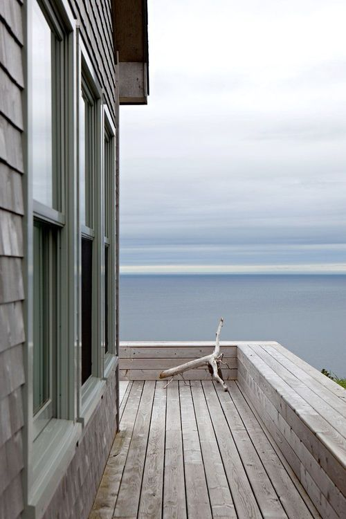 Ocean. There's a piece of wood on the wooden deck of the wooden house. Cool.