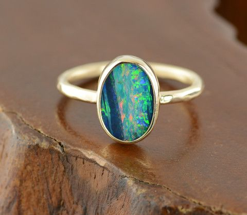 This ring features a stunning Black Opal. The colors in the opal are amazing, ranging from blue, green to pink and purple. This ring is so simple and timeless, you can wear this ring forever.The opal has been set into a solid 14k gold se...