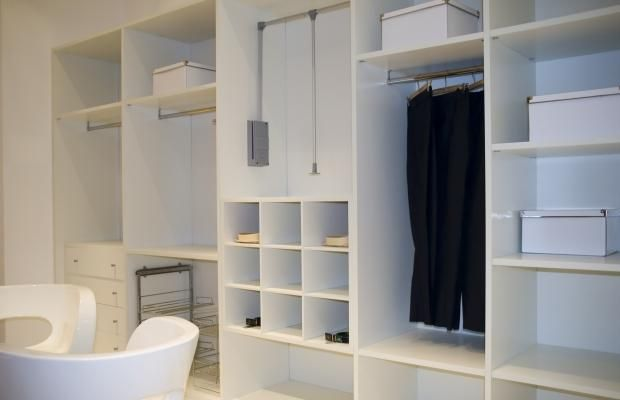 Closet accessories add function to this contemporary closet organizer. Drawers, slide out metal racks, a garment lift and clothing cubbies create clean, eye pleasing lines and make use of all the wall space. Brushed nickel hardware accents the white for a subtle touch of color without distracting from the function