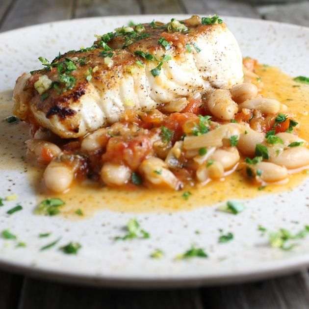 Pan Seared Halibut: seared to perfection in sautéed onions, garlic, cherry tomatoes, & cannellinis. Finished w/Gremolata of garlic, lemon & parsley.