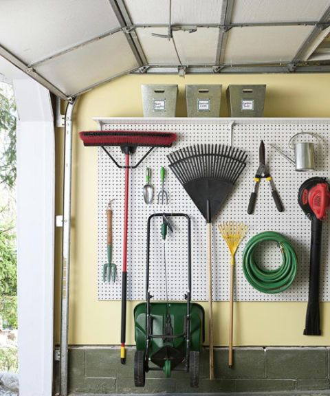A wall-mounted pegboard provides a versatile way to store garden tools, as seen on Good Housekeeping. Bins of a shelf above provide storage for loose items.   20+ Clever Ideas for a Super Organized Garage