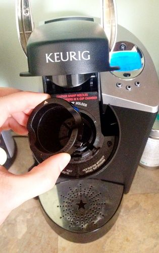 Open the top of your brewer and remove the K-cup holder. CAUTION: There's are two sharp needles in there. Be careful.
