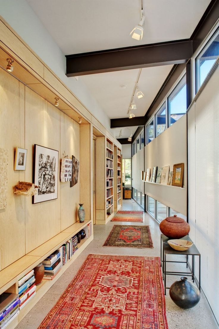I don't care for the rugs, but I love how this hallway provides beautifully integrated gallery and bookshelf space, and a lovely combination of natural and artificial illumination.