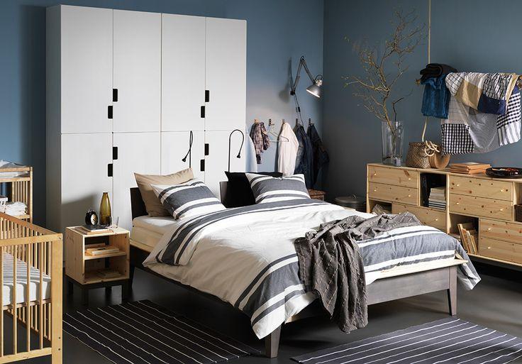 Spálňa s posteľou IKEA, príručnými stolíkmi a komodou, všetko z masívneho dreva.