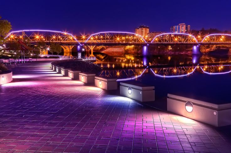The illuminated walkways of River Landing along the South Saskatchewan River.  The lights or the Traffic Bridge (or Victoria Bridge) also give life to the area.