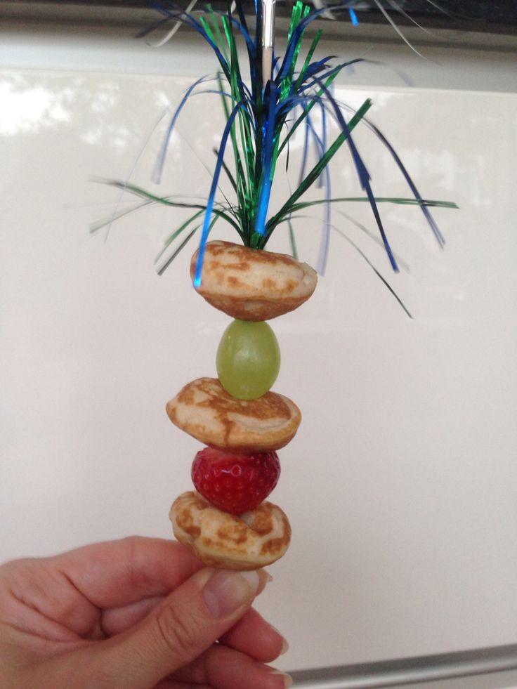 Poffertjes met fruit op een feestelijk stokje.