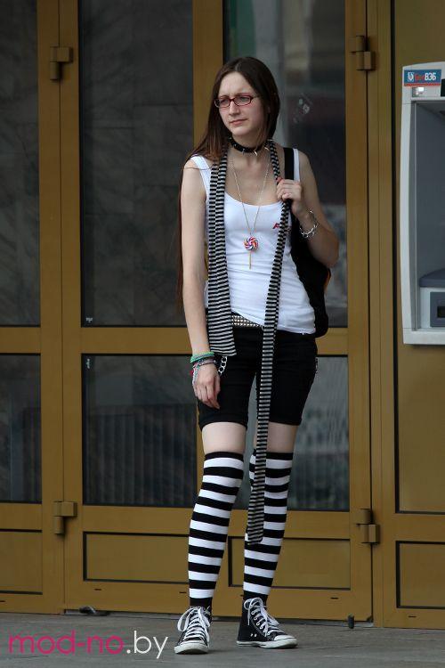 Уличная мода уходящего лета (наряды и образы на фото: белая майка, чёрно-белый полосатый шарф, чёрные шорты, чёрные кеды, белый шнурок, чёрно-белые полосатые чулки)